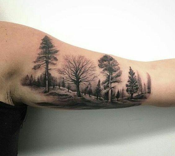 Тату лес на бицепсе мужчины