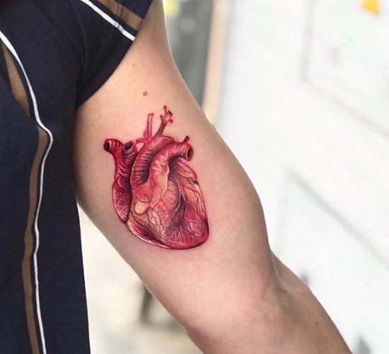 Татуировка сердце в реализме на бицепсе мужчины