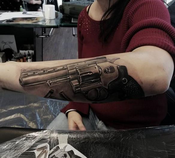 Тату револьвер на предплечье левой руки у девушки